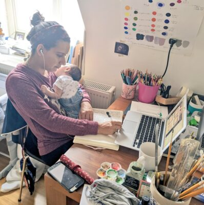 an image of Nami, illustrating in front of a laptop, covered in lots of art tools and ephemera, cradling a newborn baby